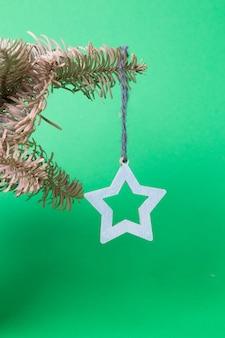 녹색 표면에 장식 가문비 나무 가지에 매달려 별 모양의 크리스마스 트리 장난감