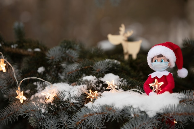 A christmas tree toy in a medical mask sits on the branches of a snow-covered christmas tree
