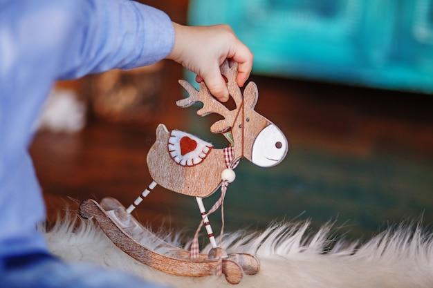 小さな子供の手にクリスマスツリーのおもちゃのムース