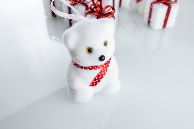 Christmas tree toy white bear near christmas gift boxes with ribbon