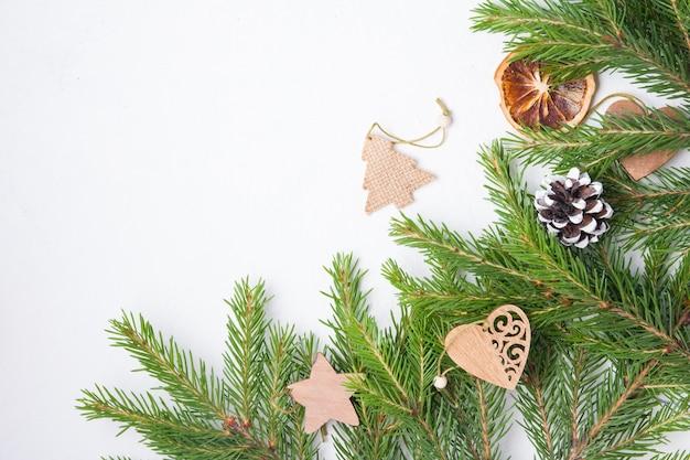 Елочные игрушки и натуральные еловые ветки на белом фоне, вид сверху, самодельные экологически чистые елочные игрушки на свежих еловых ветках