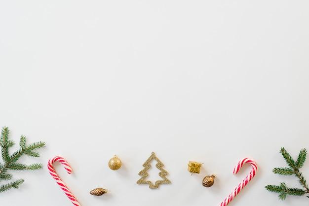 Елочные игрушки, елочные игрушки в форме ёлки, еловые ветки на белом фоне по горизонтали с копией пространства. рождественская и новогодняя открытка