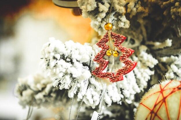 クリスマスツリーのおもちゃの装飾と雪に覆われたクリスマスツリーの枝のクローズアップ