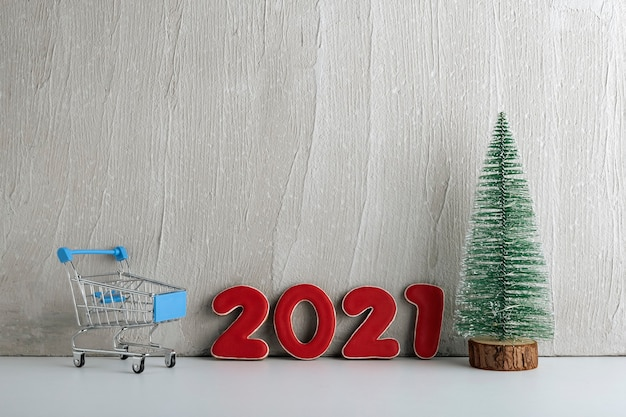 Christmas tree, trolley cart and numbers 2021 on light background. shopping for the new year. copy space.