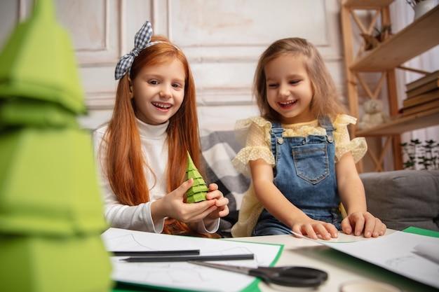 クリスマスツリー。二人の小さな子供たち、創造性のある女の子たち。幸せな子供たちは、ゲームや新年のお祝いのために手作りのおもちゃを作ります。少し白人モデル。幸せな子供時代、お祝いの準備。