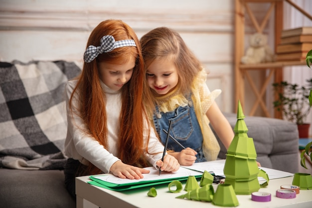 크리스마스 트리. 두 명의 어린 아이, 소녀들이 함께 창의력을 발휘합니다. 행복한 아이들은 게임이나 새해 축하를 위해 수제 장난감을 만듭니다. 작은 백인 모델. 행복한 어린 시절, 축하 준비.