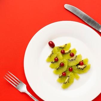 Albero di natale sul piatto bianco realizzato con diversi ingredienti