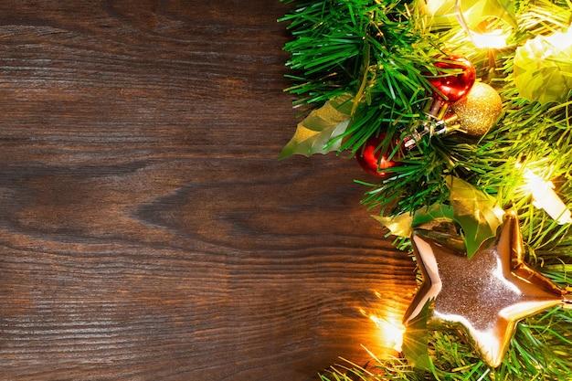 ボール、金色の星、黄色いライトの花輪のクリスマスツリーは、ダークブラウンの木製テーブルの上にあります