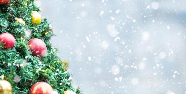 雪の雰囲気の中でボールライトとクリスマスツリー
