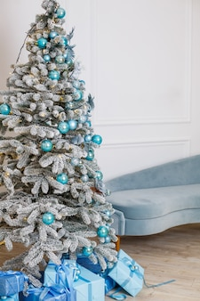 Christmas tree with blue gifts in a white christmas room. nicely decorated house with blue toys, decorated tree and gifts for christmas.
