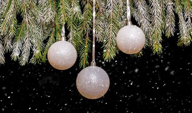 降雪時のクリスマスボールとクリスマスツリー