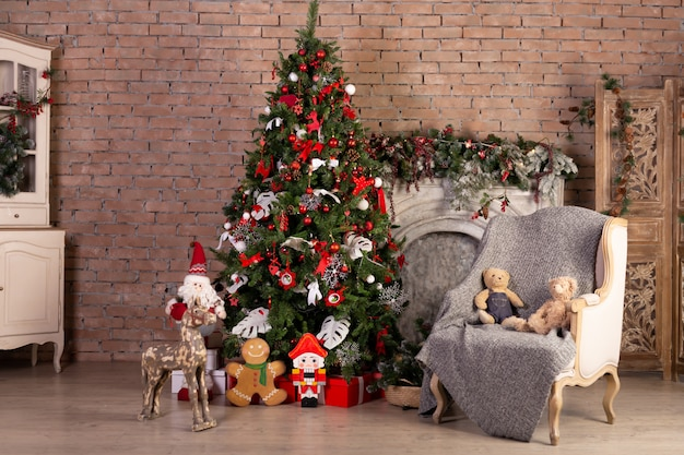 Christmas tree with colorful balls and gift boxes over brick wall. new year christmas concept. decoration. indoor photo. interior.