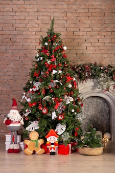 Christmas tree with colorful balls and gift boxes over brick wall. new year christmas concept. decoration. indoor.