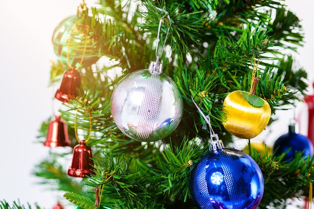 Christmas tree with colorful balls and gift boxes isolated on white