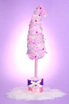Рождественская елка с изогнутым кончиком на сиреневом фоне