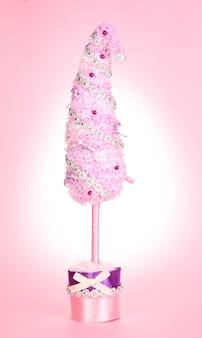 Рождественская елка с изогнутым кончиком на розовом фоне