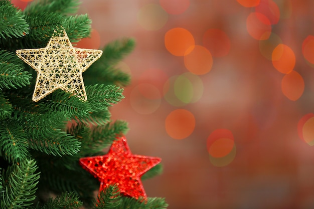 Christmas tree with decor on bright surface, closeup