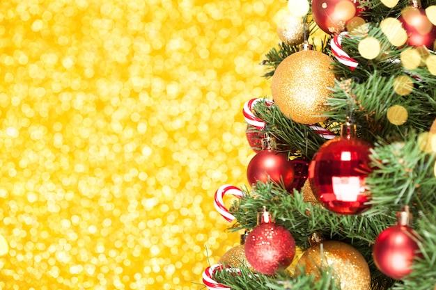 Новогодняя елка с украшениями на блестящей золотой поверхности