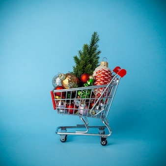 Christmas tree with decorations in a supermarket cart. christmas shopping and sale concept