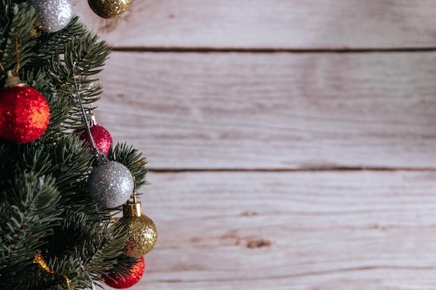 木製の背景に装飾的なボールとクリスマスツリー。スペースをコピーします。セレクティブフォーカス。