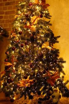 暖かい家のインテリアにお祝いの装飾が施されたクリスマスツリー。
