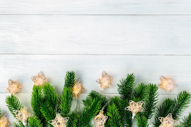 Christmas tree with garland lights at the bottom of white wooden background. merry christmas and happy new year backdrop, top view. beautiful blank frame border with copy space.