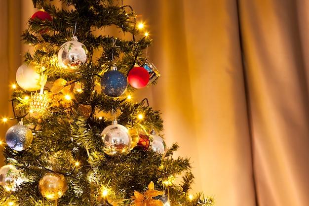 花輪と家の装飾が施されたクリスマスツリー。装飾的でお祝いの緑の木