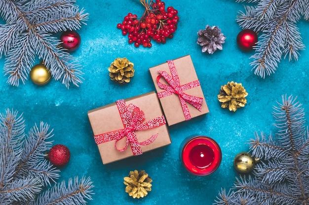 青い背景の上の贈り物とクリスマスツリー。赤と金のボールで構成