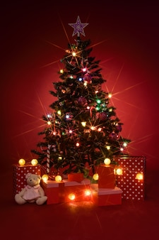 Christmas tree with gifts on red background