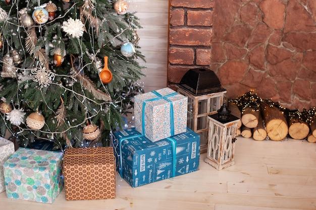 화환과 장작이있는 벽난로 근처의 선물이 담긴 크리스마스 트리