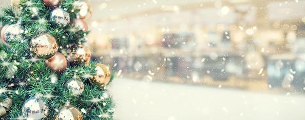 ショッピングモールの金の装飾が施されたクリスマスツリー-パノラマのぼやけたバナー。