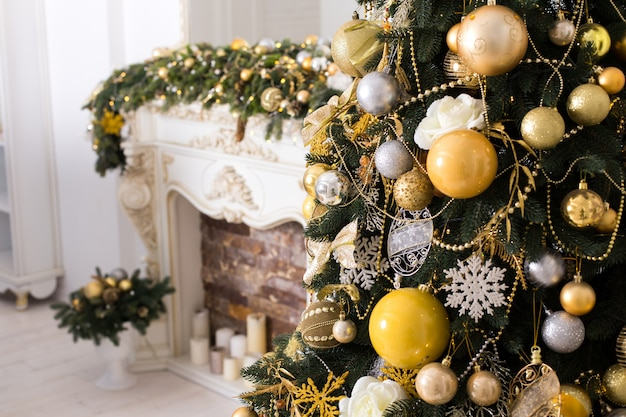 Christmas tree with golden christmas balls near decoreted fireplace.