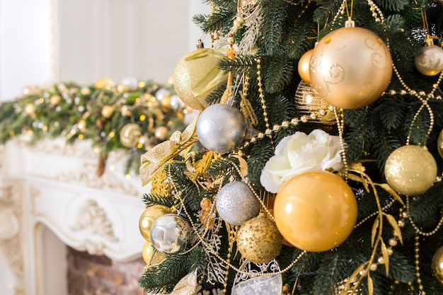 Christmas tree with golden and white christmas balls near decoreted fireplace.