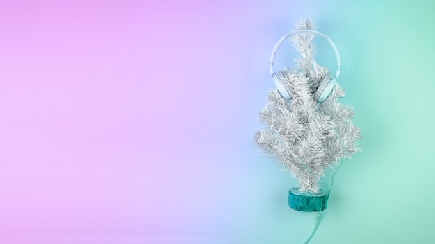 Christmas tree with headphones on pastel pink blue background