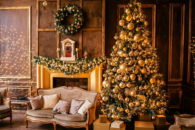 Christmas tree with lights and golden decoration and fireplace in living room.