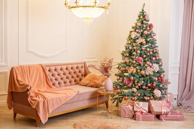 白いクリスマスの部屋にピンクの贈り物とクリスマスツリー。ピンクのおもちゃで飾られた木とクリスマスのプレゼントで素敵に装飾された家。