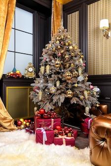 Рождественская елка с настоящими коробками в гостиной. новый год и концепция интерьера рождественской комнаты. праздничные украшения и украшения. пора отмечать зимние праздники.