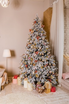 Christmas tree with presents. holiday decoration. elegant christmas tree with white and pink toys in the luxury apartments.great beautifully decorated tree with pink baubles, ribbons, snowflakes