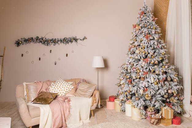 Christmas tree with presents. holiday decoration.elegant christmas tree with white and pink toys in the luxury apartments.great beautifully decorated tree with pink baubles, ribbons, snowflakes