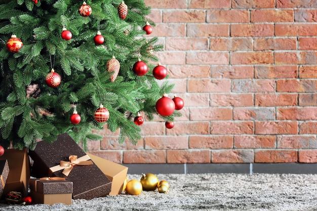 Рождественская елка с подарками в комнате на фоне кирпичной стены