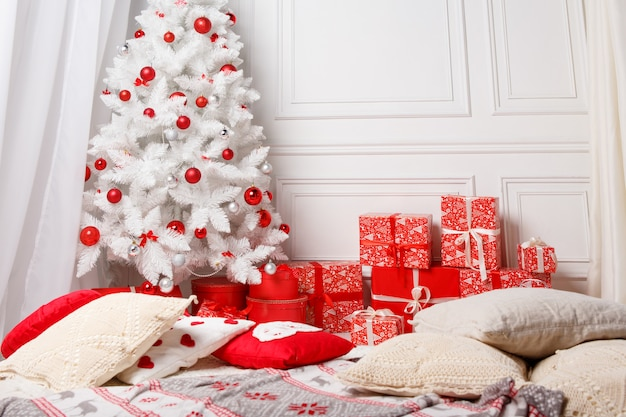 Christmas tree with presents underneath in white living room