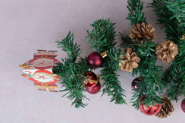Рождественская елка с красными шарами и шишками на серой поверхности
