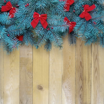 Christmas tree with red decoration on wooden