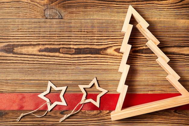 Рождественская елка с красной лентой и звездами на деревянном фоне с копией пространства
