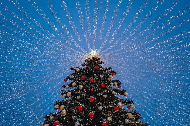 お祝いの夜の街ボケの花輪の赤いおもちゃのボールの星と金色のライトとクリスマスツリー