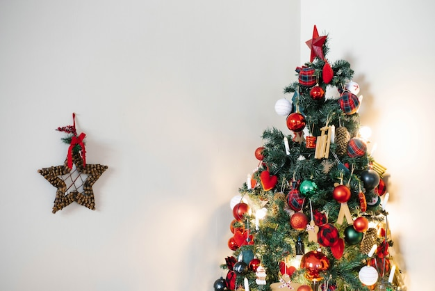 빨간 장난감 및 가벼운 벽 배경에 녹색 것들 크리스마스 트리