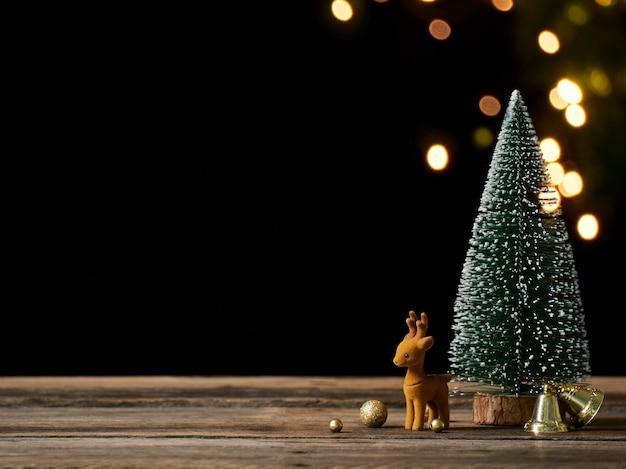 Рождественская елка с оленями на деревенском старинном деревянном столе. эффект боке, место для текста