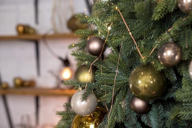 Елка с блестящими белыми, золотыми и бронзовыми шарами в гостиной
