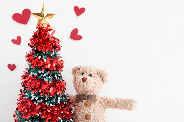 Christmas tree with a teddy bear and he play seek and hide happy feels in new year.