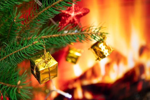 Christmas tree with toys on the background of a fireplace with fire